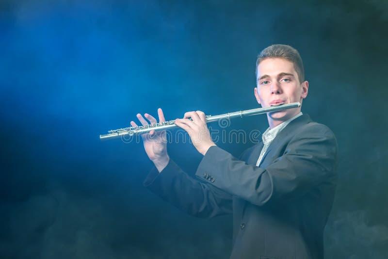 Een jonge musicus speelt muziek op een fluit Blauwe verlichting Rook tegen een donkere achtergrond zoals mist De ruimte van het e royalty-vrije stock afbeelding