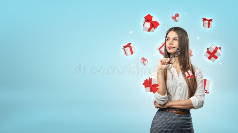 Een jonge onderneemster bevindt zich denkend terwijl de kleine witte en rode giftdozen rond haar hoofd vliegen royalty-vrije stock afbeelding