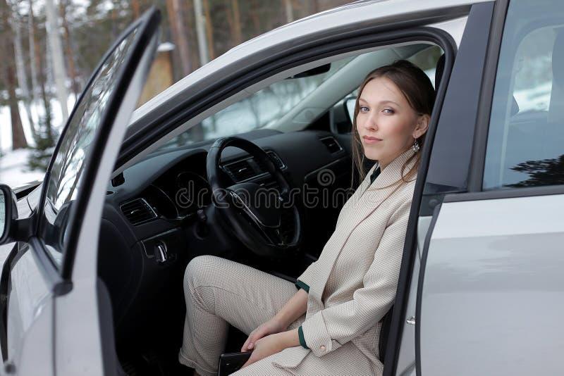 Een jonge onderneemster gaat een auto weg stock foto's