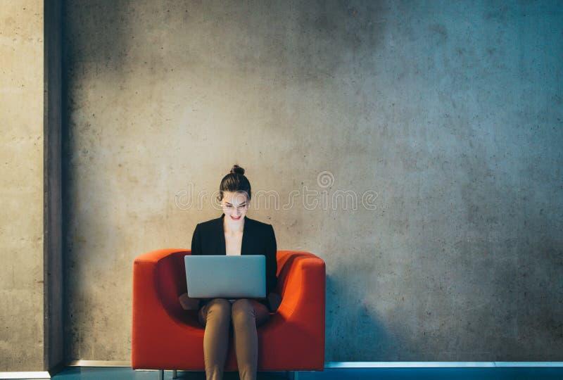 Een jonge onderneemster met laptop zitting op rode leunstoel in bureau De ruimte van het exemplaar royalty-vrije stock afbeeldingen