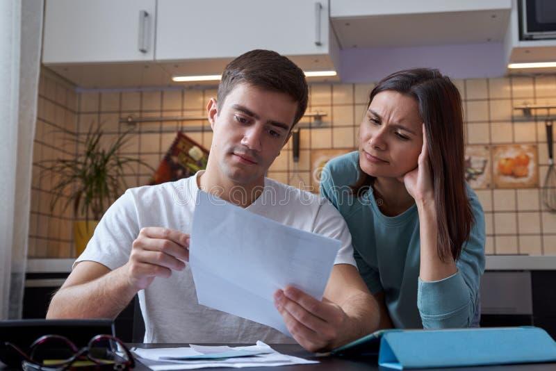 Een jonge paarzitting bij een lijst in de keuken begrijpt de financiën van een jonge familie, die rekeningen en belastingsdocumen stock afbeeldingen