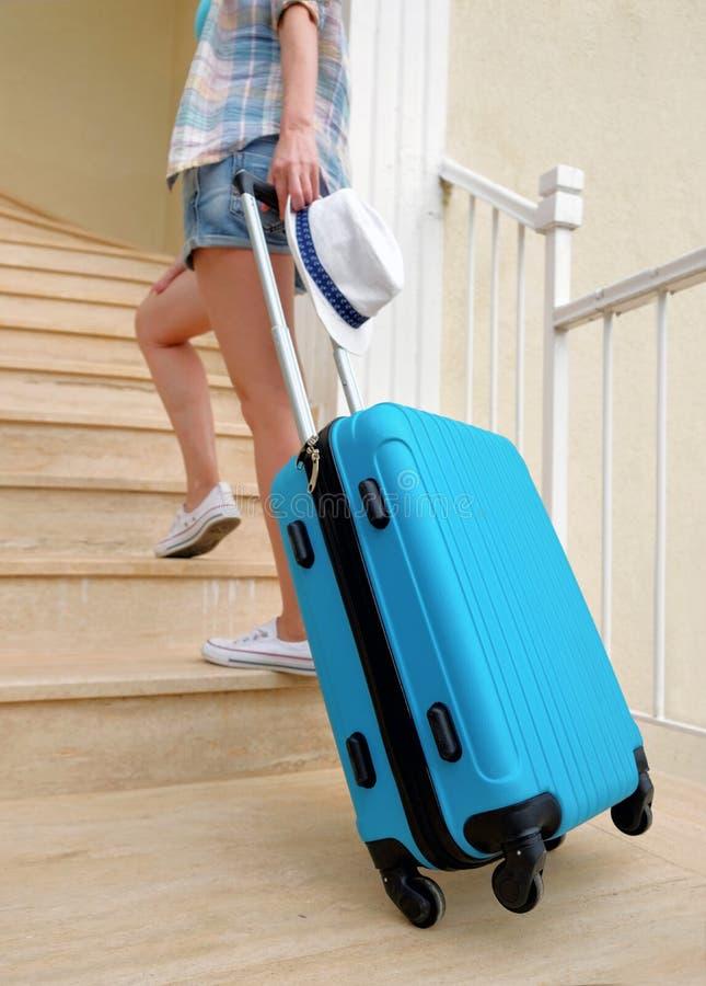 Een jonge reisvrouw in witte tennisschoenen draagt omhoog een blauwe koffer de treden aan het hotel stock afbeelding