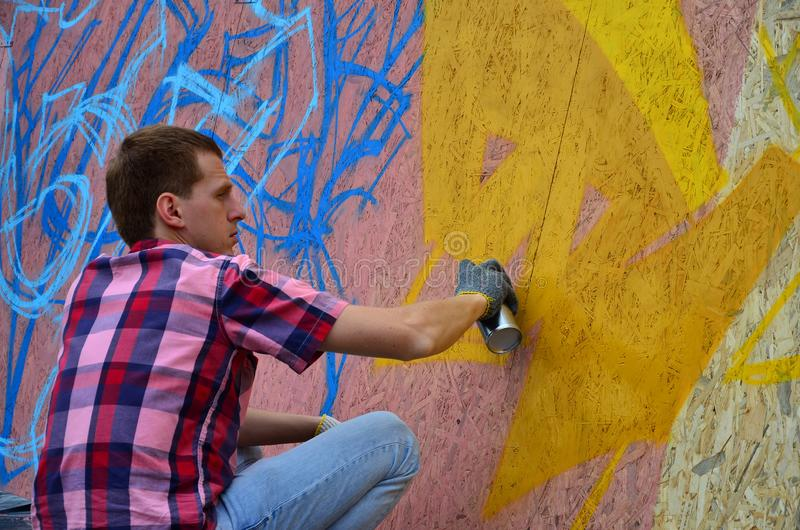 Een jonge roodharige graffitikunstenaar schildert een nieuwe graffiti op de muur royalty-vrije stock foto