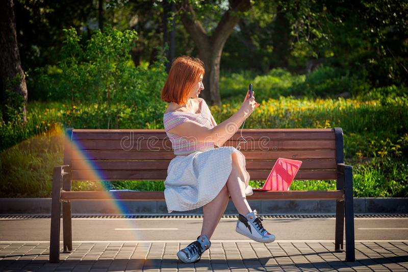 Een jonge roodharige vrouw in park stock foto's