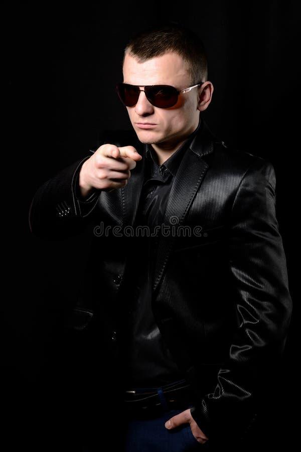 Een jonge ruwe kerel in een jasje en een band toont een wijsvinger aan de camera stock foto's