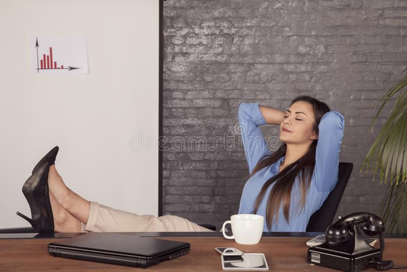 Een jonge secretaresse geniet van een vrij ogenblik, rust op het werk royalty-vrije stock foto's