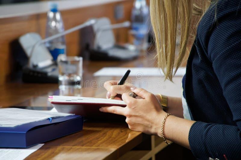 Een jonge secretaresse met een gouden armband schrijft nota's in een agenda en toont een onfatsoenlijk gebaar aan haar werkgever royalty-vrije stock foto