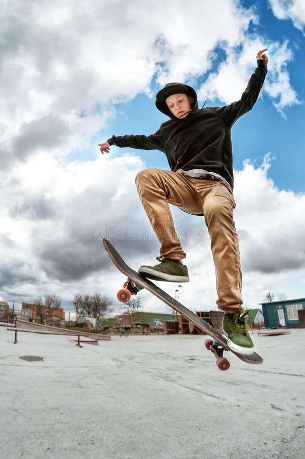 Een jonge skateboarder maakt Wallie in een skatepark, die op een skateboard in de lucht met een staatsgreep springen royalty-vrije stock foto's