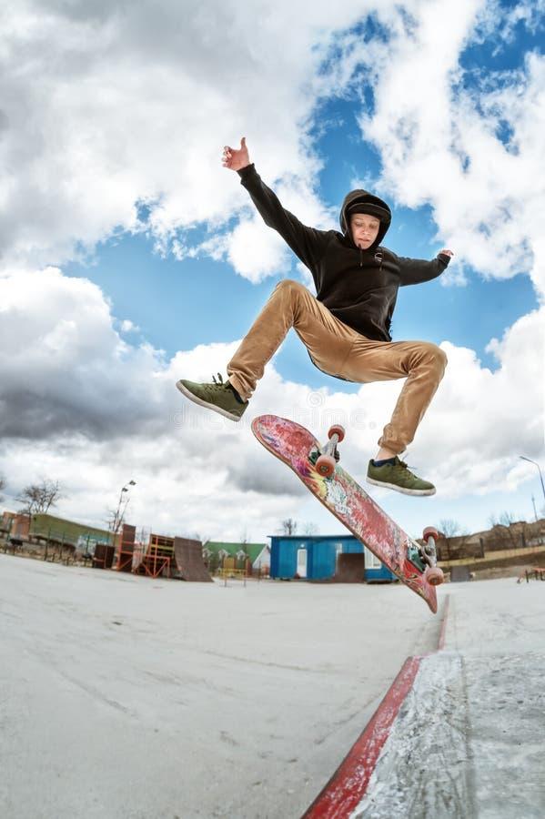 Een jonge skateboarder maakt Wallie in een skatepark, die op een skateboard in de lucht met een staatsgreep springen royalty-vrije stock fotografie