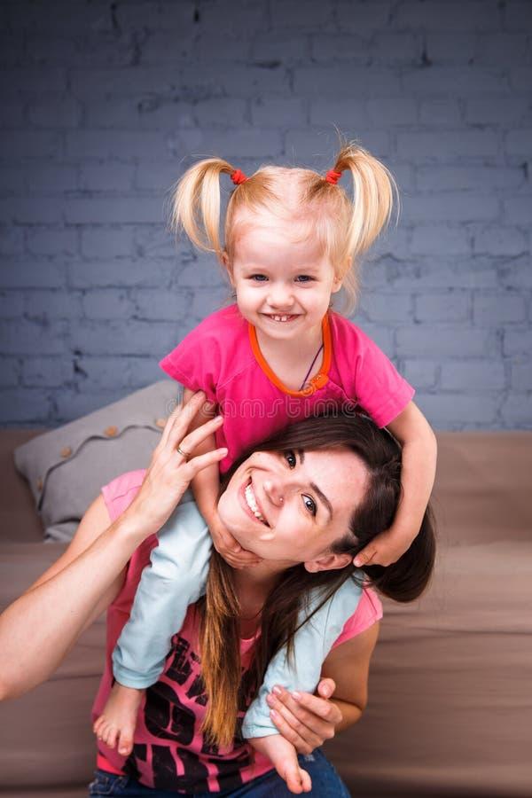 Een jonge slanke mooie moeder met haar blonde dochter op haar schoudersspel, geniet van en stelt in de teams tevreden dichtbij de royalty-vrije stock afbeelding