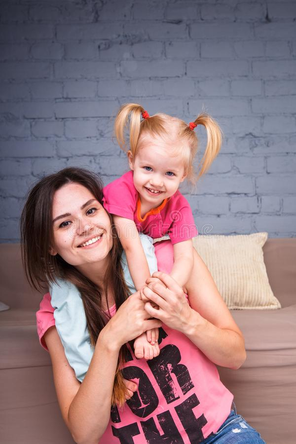 Een jonge slanke mooie moeder met haar blonde dochter op haar schoudersspel, geniet van en stelt in de teams tevreden dichtbij de stock afbeeldingen