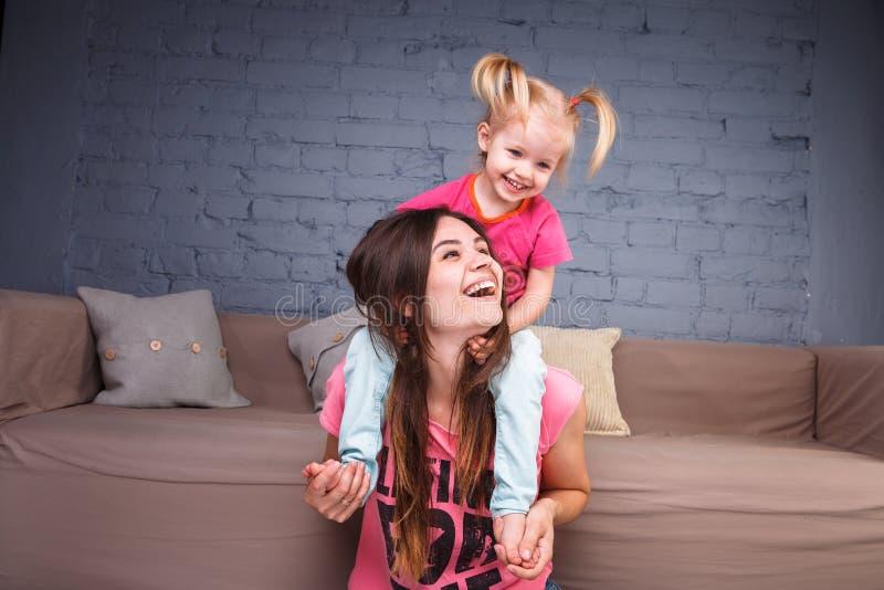 Een jonge slanke mooie moeder met haar blonde dochter op haar schoudersspel, geniet van en stelt in de teams tevreden dichtbij de stock foto