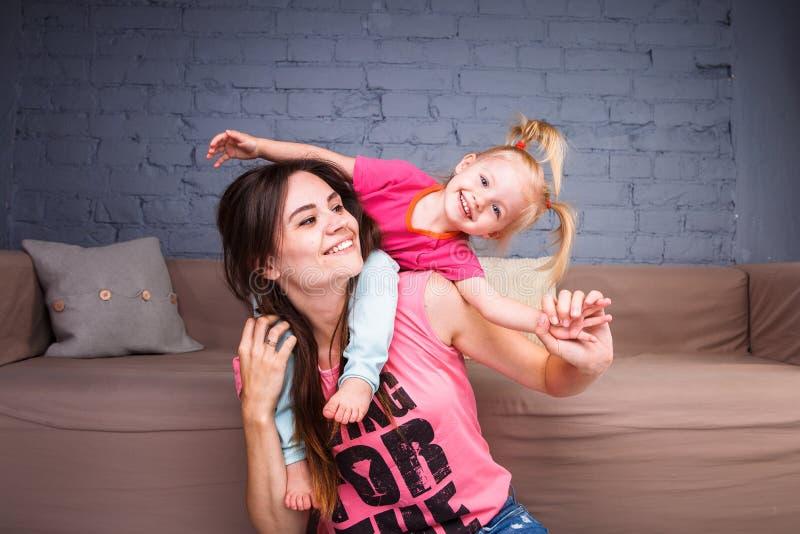 Een jonge slanke mooie moeder met haar blonde dochter op haar schoudersspel, geniet van en stelt in de teams tevreden dichtbij de stock afbeelding