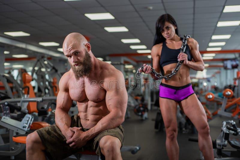 Een jonge spierkerel zit op een bank in de gymnastiek en rust na een training Erachter is een spier donker-haired meisje stock foto's
