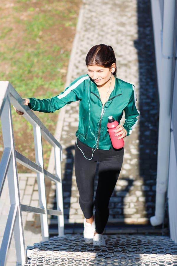 Een jonge sportieve vrouw met perfect lichaam die oefeningen op treden doen openlucht royalty-vrije stock afbeeldingen