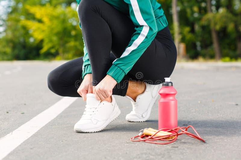 Een jonge sportieve vrouw verbindt schoenveters op tennisschoenen Een meisje met perfect lichaam die oefeningen doen stock afbeeldingen