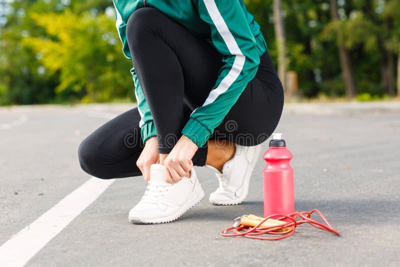 Een jonge sportieve vrouw verbindt schoenveters op tennisschoenen Een meisje met perfect lichaam die oefeningen doen stock fotografie