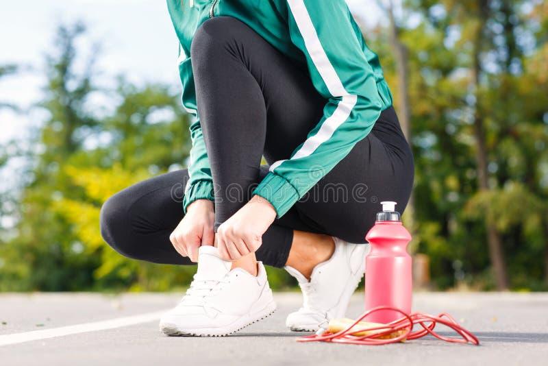 Een jonge sportieve vrouw verbindt schoenveters op tennisschoenen Een meisje met perfect lichaam die oefeningen doen stock foto