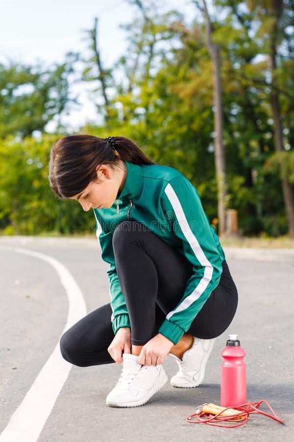 Een jonge sportieve vrouw verbindt schoenveters op tennisschoenen Een meisje met perfect lichaam die oefeningen doen royalty-vrije stock foto's