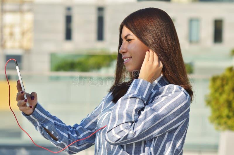 Een jonge studente van Aziatische verschijning gekleed in een gestreept overhemd neemt een selfie en luistert aan muziek stock foto