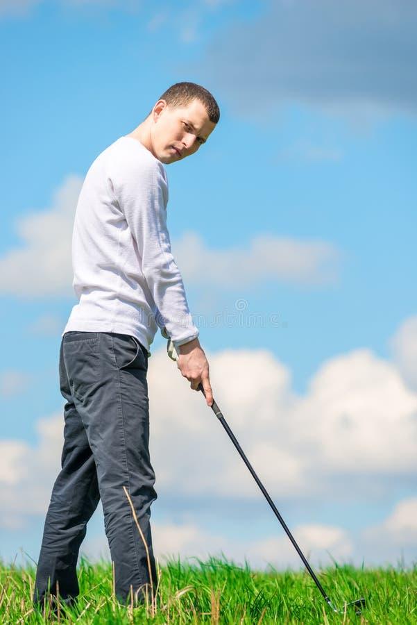 Een jonge succesvolle golfspeler treft voorbereidingen om de bal met een golf c te raken royalty-vrije stock foto's