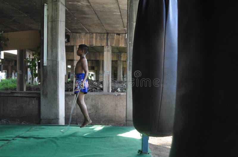 Een jonge Thaise Thaise vechter van Muay springt het koord bij een het in dozen doen gymnastiek onder een brug in Minburi, Thaila stock fotografie