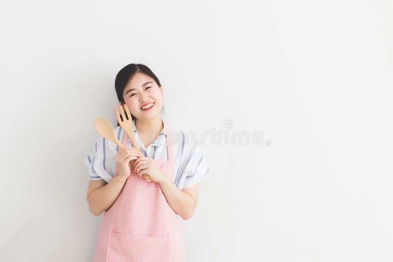 Een jonge Thaise vrouw, witte huid die, lang haar, een toevallige kleding en een roze schort dragen, die een keukengerei op een w royalty-vrije stock fotografie