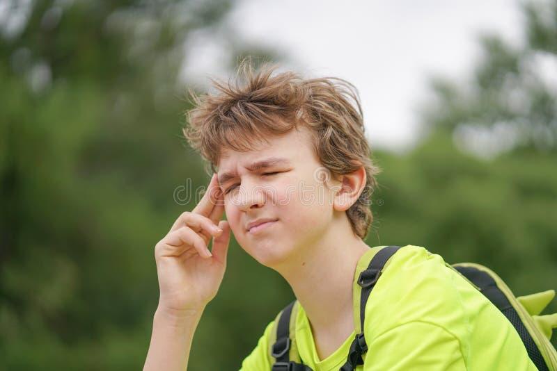 Een jonge tienerkerel lijdt aan een hoofdpijn hij houdt zijn handen aan zijn hoofd en huiveringen van ongemak, zittend op de aard royalty-vrije stock afbeelding