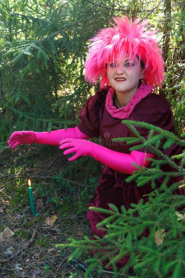 Een jonge tovenarij in paarse kleding vormt een kaars die in de grond terecht komt Verticale foto stock foto