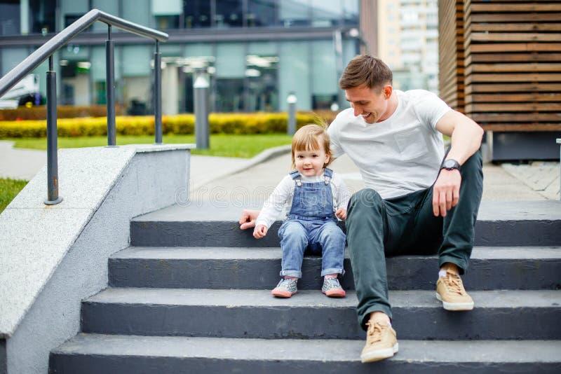 Een jonge vader en een kleine dochter rusten op de stappen in het stadspark royalty-vrije stock afbeelding