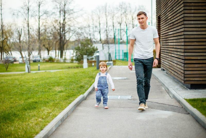 Een jonge vader met zijn dochter op een gang in het stadspark stock foto's