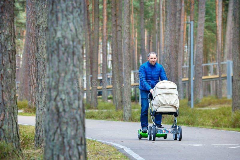 Een jonge vader op de raad van de gyroscoopautoped met een wandelwagen loopt door het de herfstpark stock afbeelding