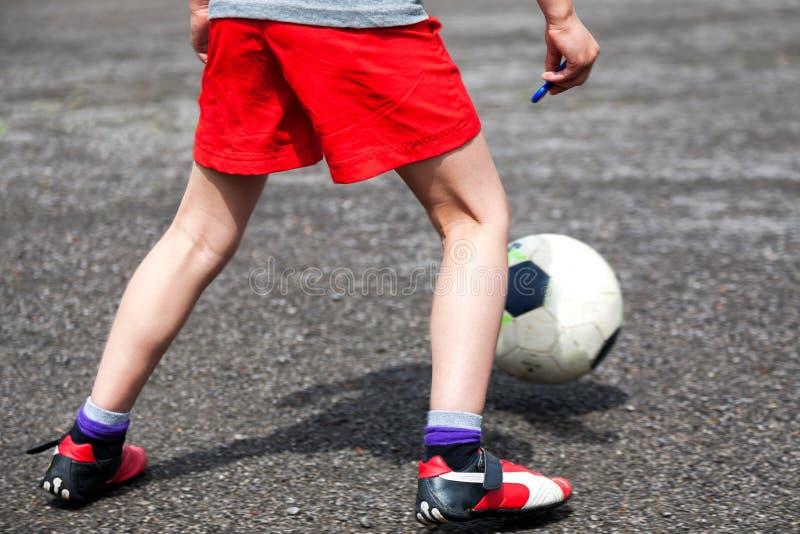 Een jonge voetballer die de bal spelen stock afbeeldingen