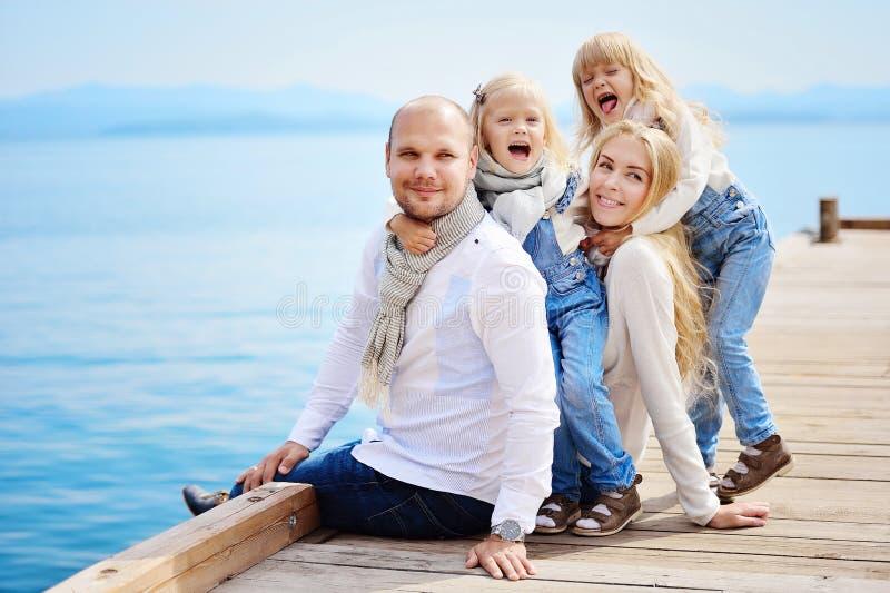 Een jonge, vriendschappelijke familie: de vader, de moeder en twee dochters zitten o stock foto