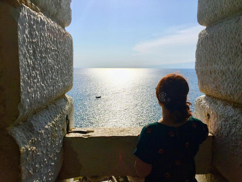 Een jonge vrouw alleen status vanaf de bovenkant van een oude steenklokketoren die uit de enorme oceaan bekijken stock afbeelding