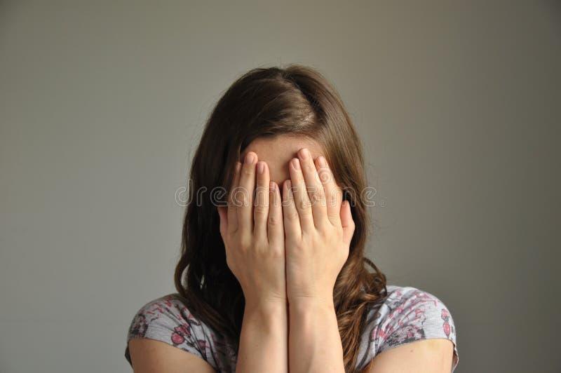 Een jonge vrouw behandelt haar gezicht met handen royalty-vrije stock afbeelding