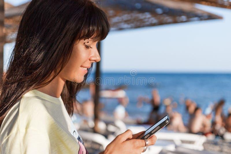 Een jonge vrouw bekijkt het telefoonscherm Op de achtergrond is een overzees strand met mensen Het concept het verre werk aangaan stock foto