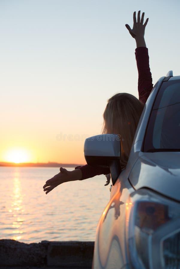 Een jonge vrouw bekijkt uit het autoraam de zonsondergang op het overzees royalty-vrije stock fotografie