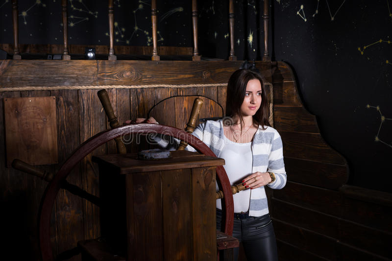 Een jonge vrouw bevindt zich bij het roer van het schip en onderzoekt royalty-vrije stock foto