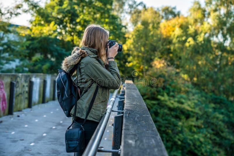Een jonge vrouw bevindt zich op een brug en neemt een beeld royalty-vrije stock fotografie