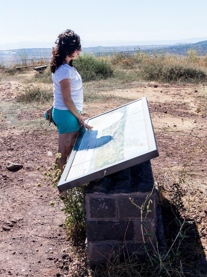 Een jonge vrouw bevindt zich op een heuvel en onderzoekt een kaart van Golan Heights stock afbeeldingen