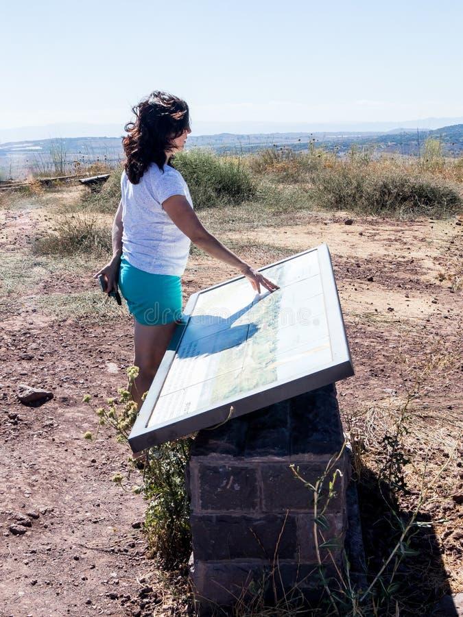 Een jonge vrouw bevindt zich op een heuvel en onderzoekt een kaart van Golan Heights stock fotografie