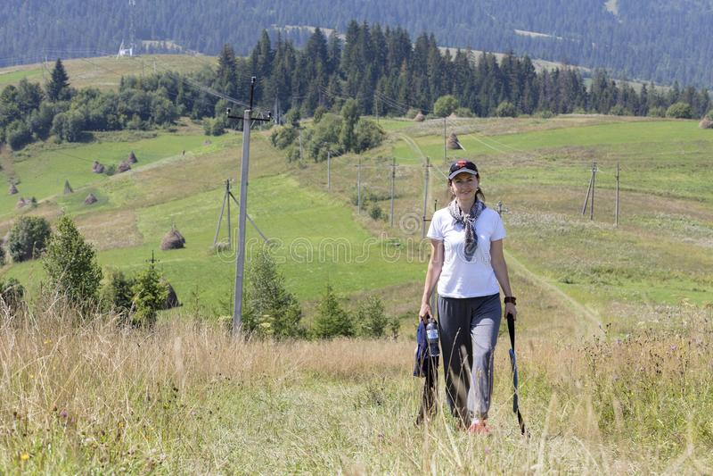 Een jonge vrouw in een blije stemming neemt op de helling in de Karpaten toe royalty-vrije stock afbeelding