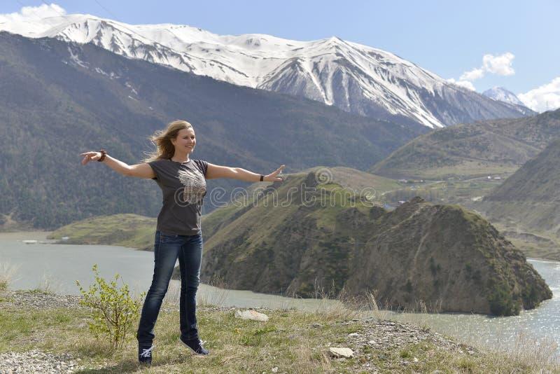 Een jonge vrouw brengt op haar tenen in evenwicht en glimlacht met genoegen stock foto