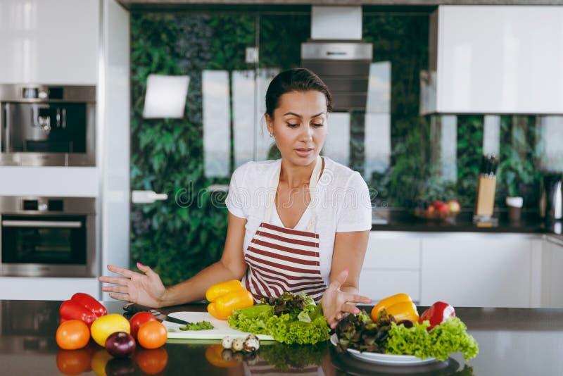 Een jonge vrouw brengt tijd thuis, in de keuken en in roo door stock fotografie