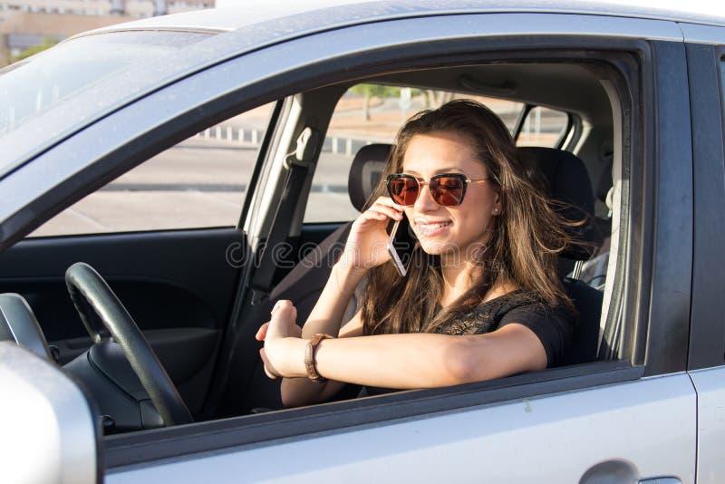 Een jonge vrouw in de auto spreekt op de slimme telefoon en de aandrijving stock fotografie