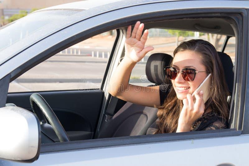 Een jonge vrouw in de auto spreekt op de slimme telefoon en de aandrijving stock foto