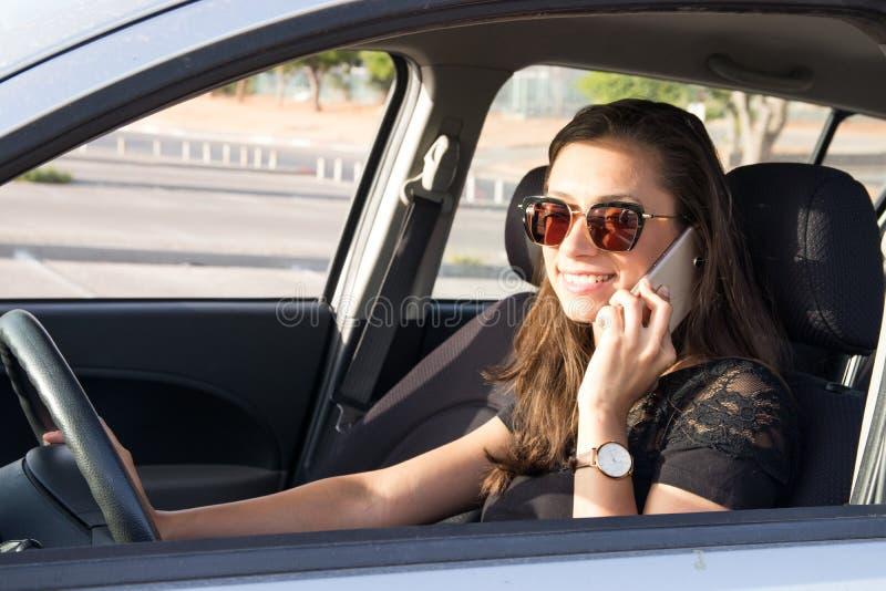 Een jonge vrouw in de auto spreekt op de slimme telefoon en de aandrijving royalty-vrije stock afbeelding