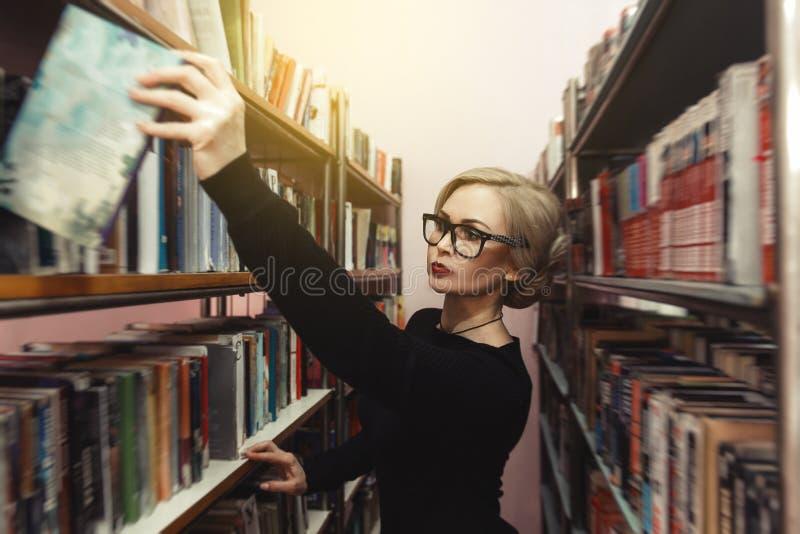 Een jonge vrouw in de bibliotheek kiest een boek royalty-vrije stock foto