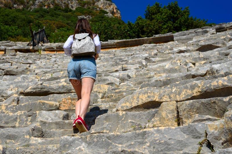 Een jonge vrouw in denimborrels en een rugzak gaat door de ruïnes van het amfitheater naar boven, een aanraking van geschiedenis, stock afbeelding